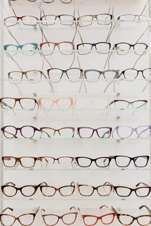 Stylish rims with lenses for vision arranged on glass shelves in ophthalmology salon