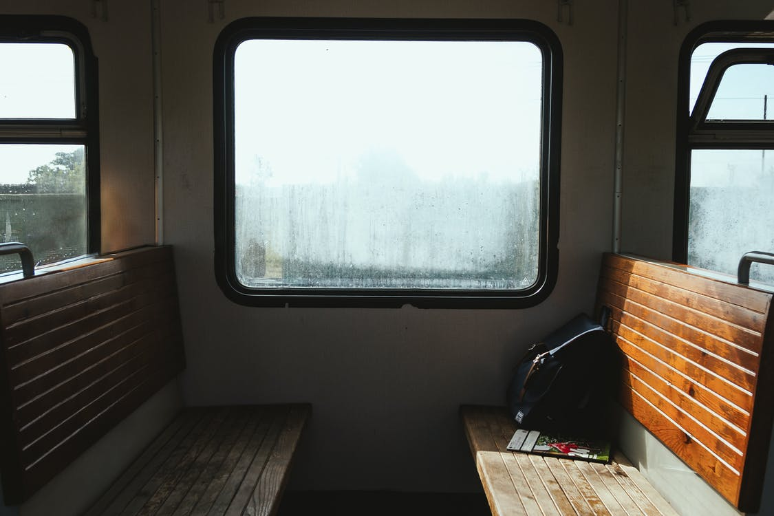 Old empty benches with backpack and magazine near shiny window in train in sunlight