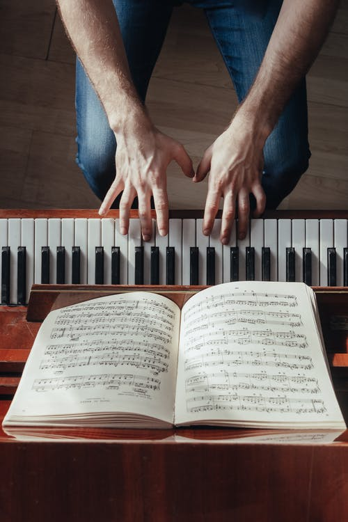 Top view of crop unrecognizable male musician plating piano with music paper on stand during rehearsal