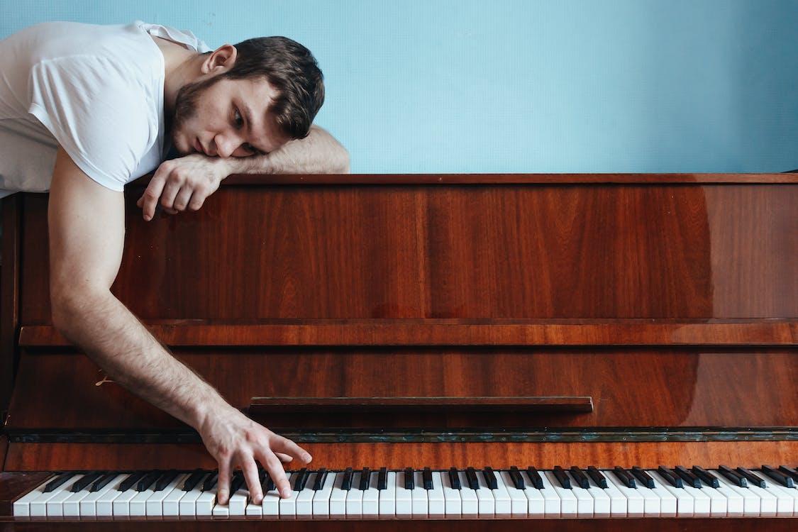 Melancholic pianist playing piano near blue wall