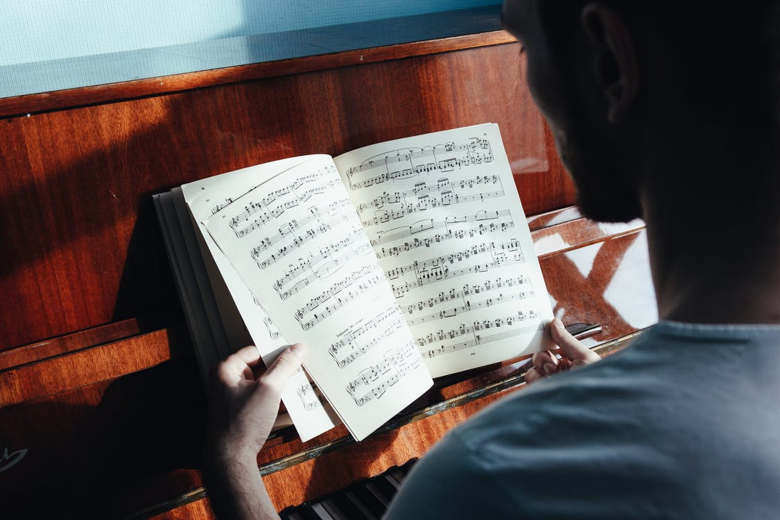 Back view of crop anonymous male pianist watching music paper with written notes near piano