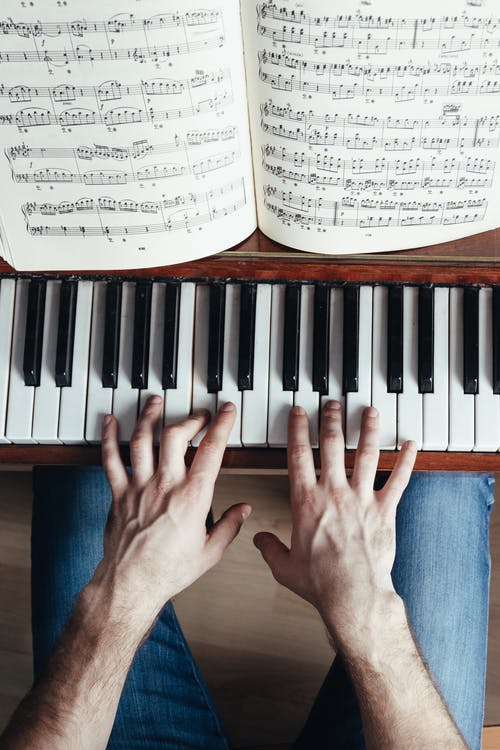 Faceless musician playing piano using music paper