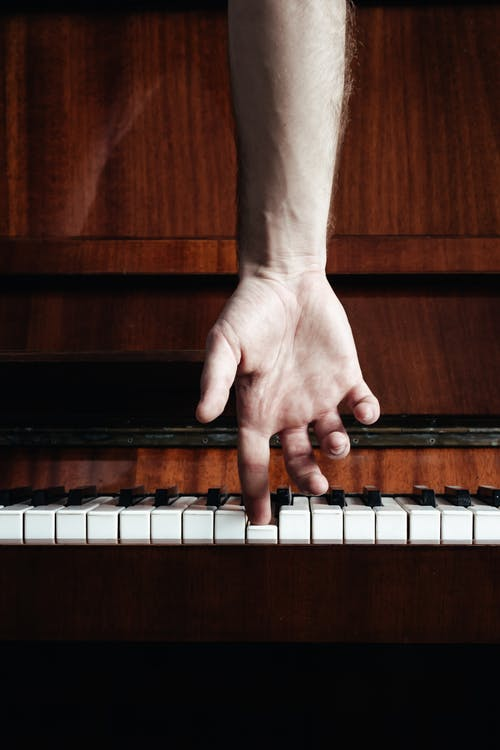 Crop musician playing piano with finger in classroom