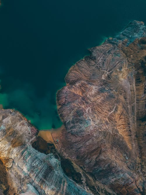Breathtaking aerial view of turquoise ocean surrounded by rough rocky mountains in sunlight