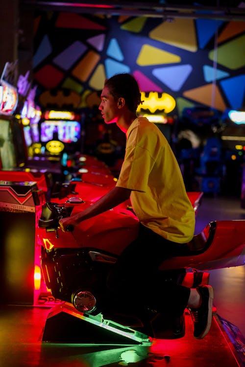 Man in Yellow Dress Shirt Playing Arcade Game