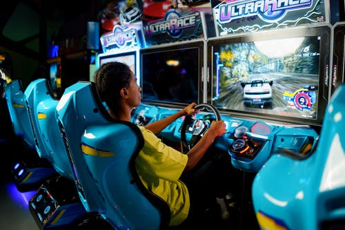 Man in Yellow Shirt Riding Blue and Yellow Arcade Game