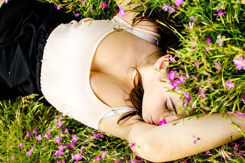 Woman Wearing White Tank Top and Black Bottoms Lying on Grass