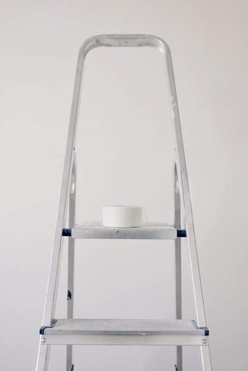 Metal ladder with roll of paper tape for renovation works in flat against white wall
