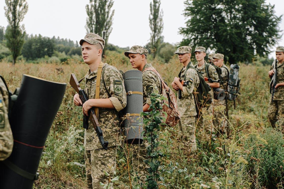 Men in Camouflage Uniform Holding Rifles
