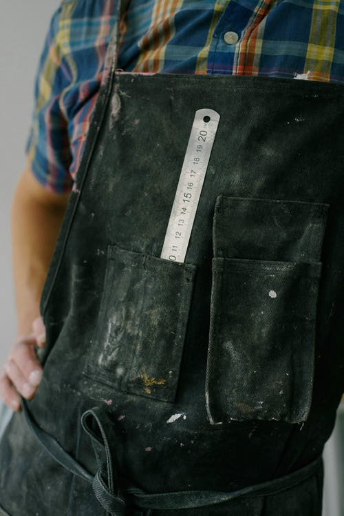 Crop anonymous male worker wearing overall with ruler in pocket during renovation works in apartment