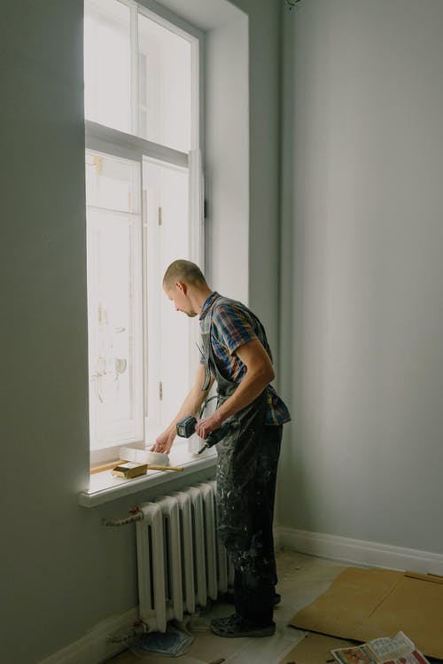 Man with screwdriver preparing for renovation in apartment