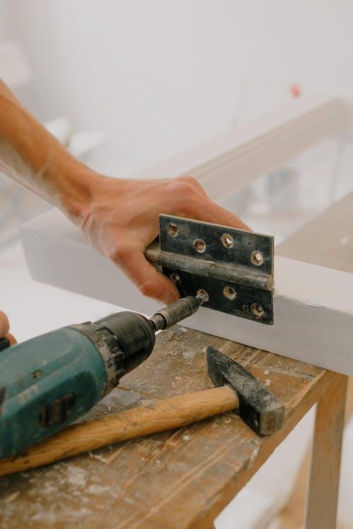 Crop handyman fastening metal hinge on white window