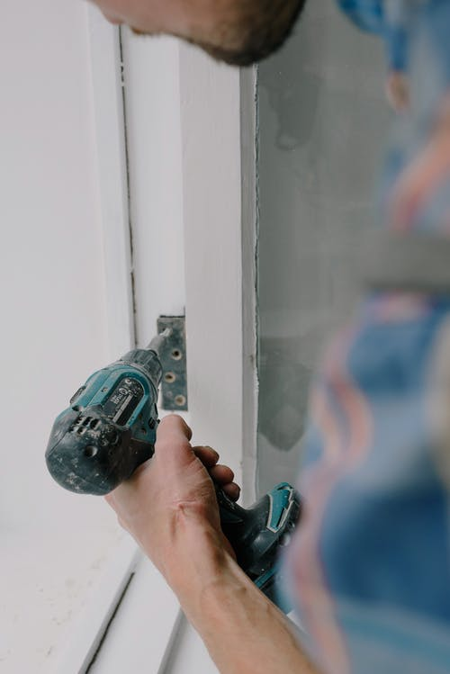 Crop bearded guy installing new wooden window with contemporary screwdriver and metal hinge during renovation process in apartment