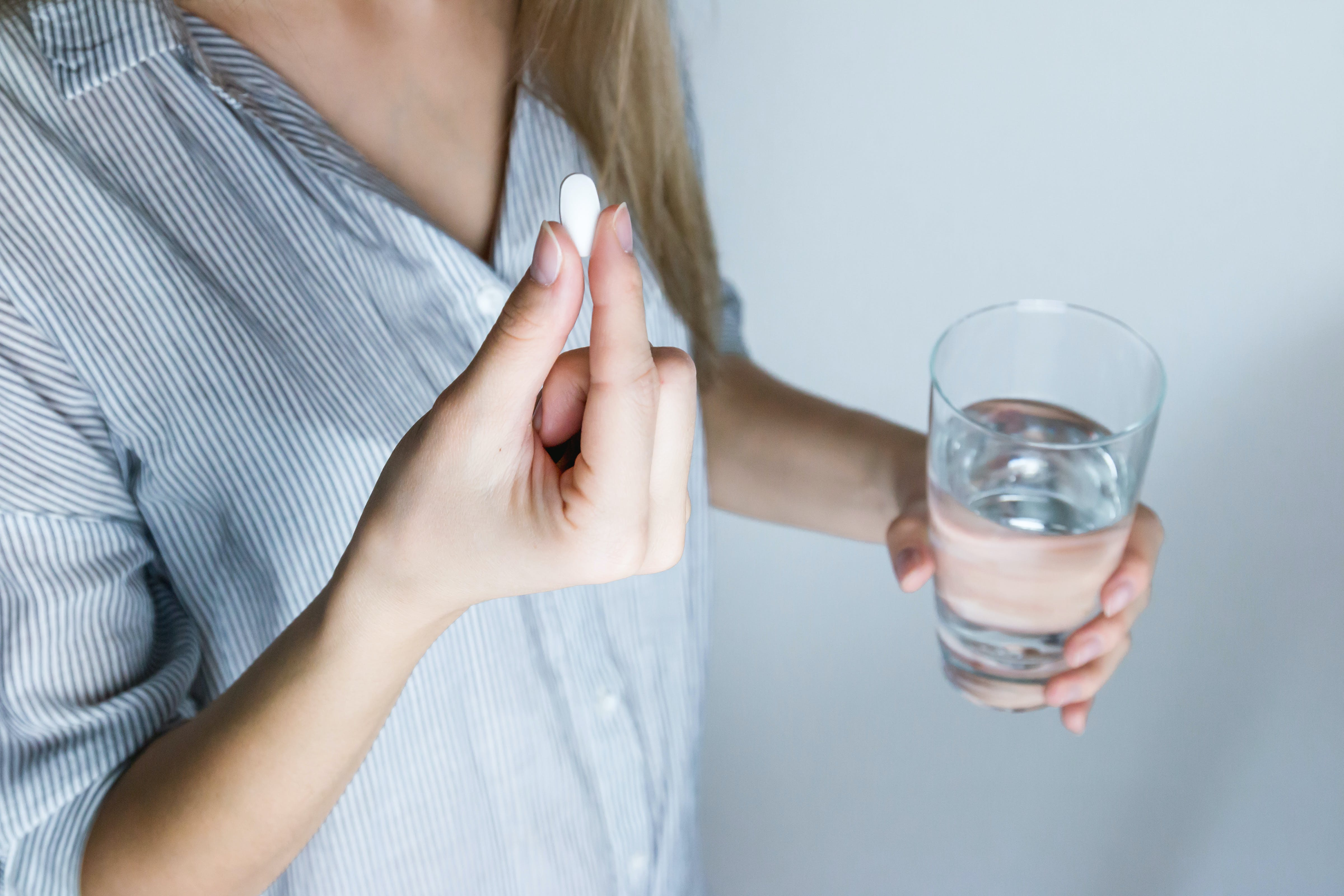 Woman Holding Half-full Glass and White Medicine Pill