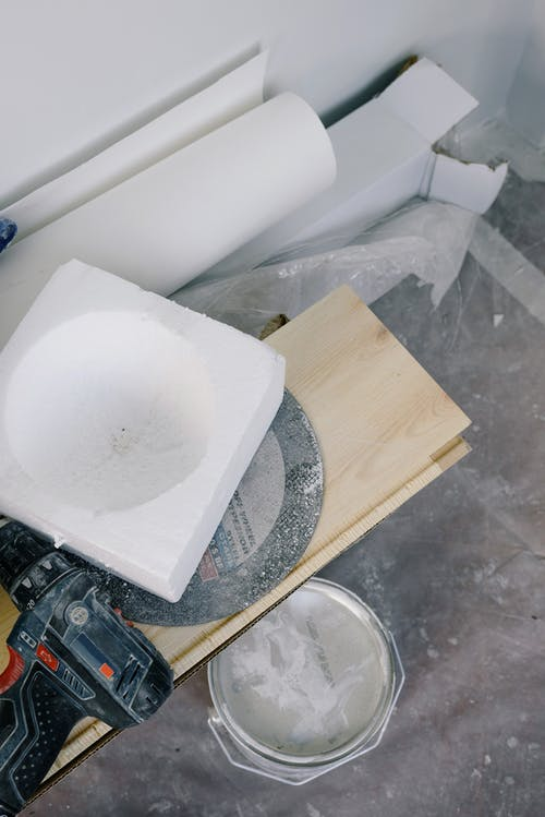 From above of bucket of white paint located under plywood plank with contemporary screwdriver and various materials for renovation