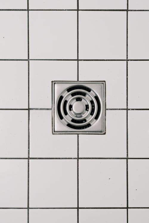 Top view of white ceramic tile floor with stainless steel square shaped cover of drain in contemporary shower