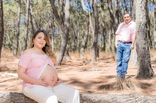 Woman in Pink Top Sitting on a Tree Log