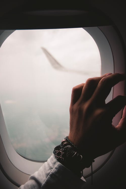Free stock photo of aeroplane, airplane window, hand, journey