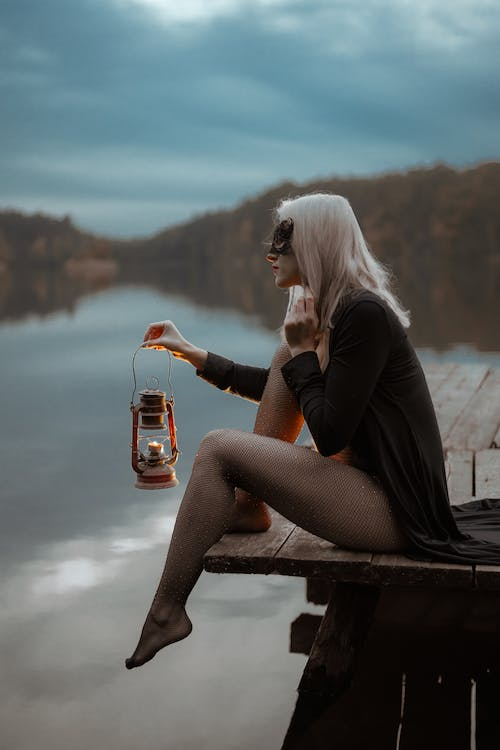 Sensual woman with lantern in mask on dock near river