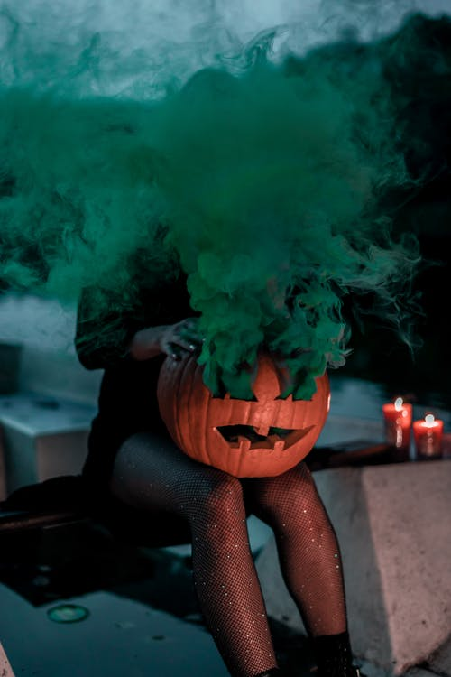 Faceless woman with jack lantern and colored smoke in twilight