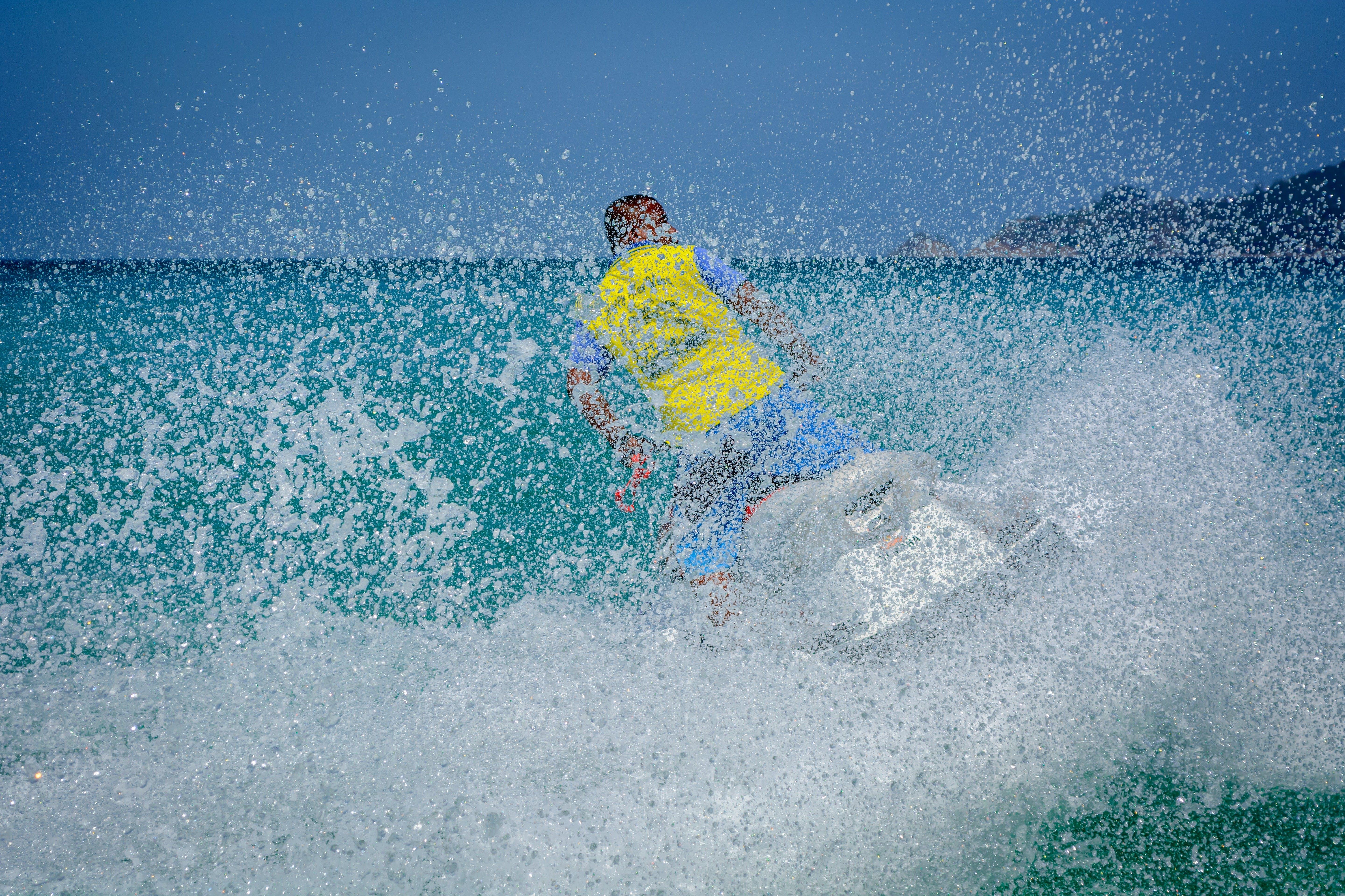 Man in Yellow Shirt Using Personal Watercraft