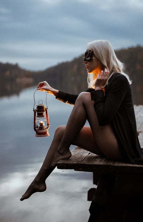 Side view of young barefoot female in carnival mask touching hair on dock near river while looking forward in evening