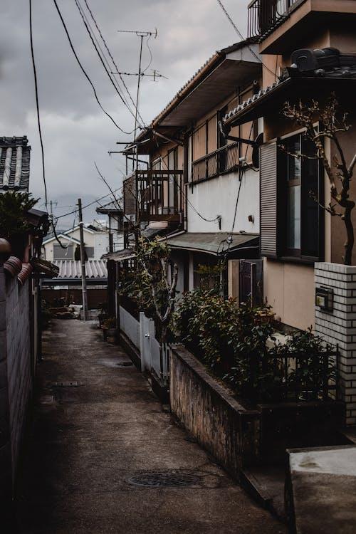 Homme En Veste Noire Debout à Côté Du Bâtiment En Béton Blanc