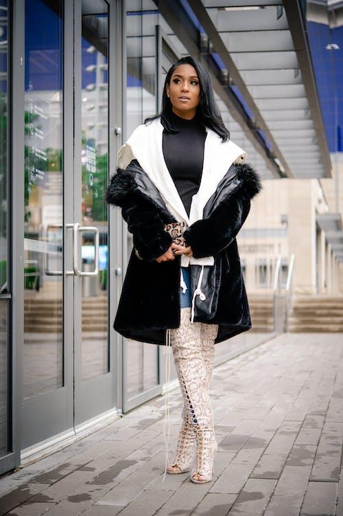 Stylish ethnic model in luxury apparel on pavement near building