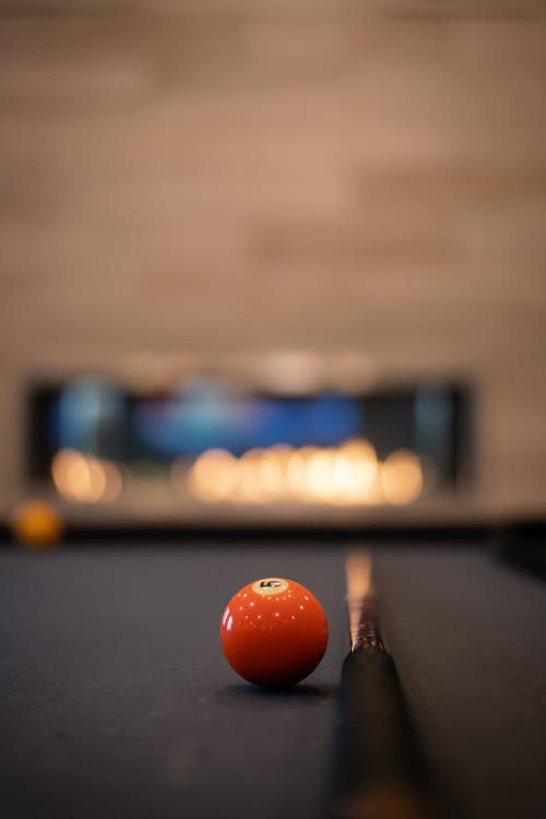 Bright billiard ball and cue on pool table