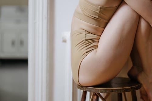 Woman in Beige Underwear Sitting on Brown Wooden Chair