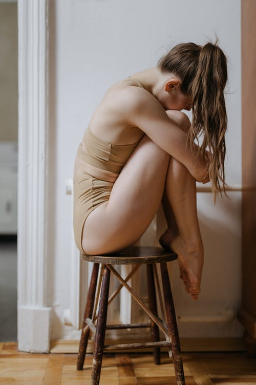 Woman in Beige Underwear Sitting on Brown Wooden Stool