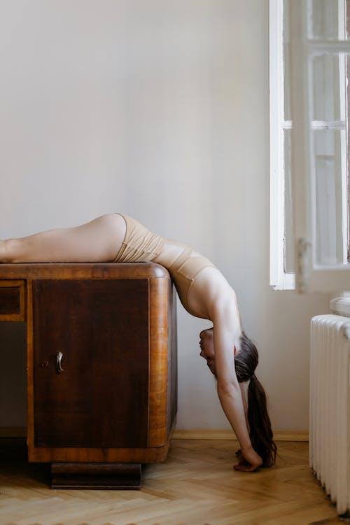 Woman Lying on Brown Wooden Desk