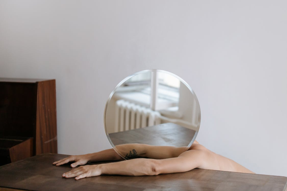 Person Holding Round Mirror on Brown Wooden Table