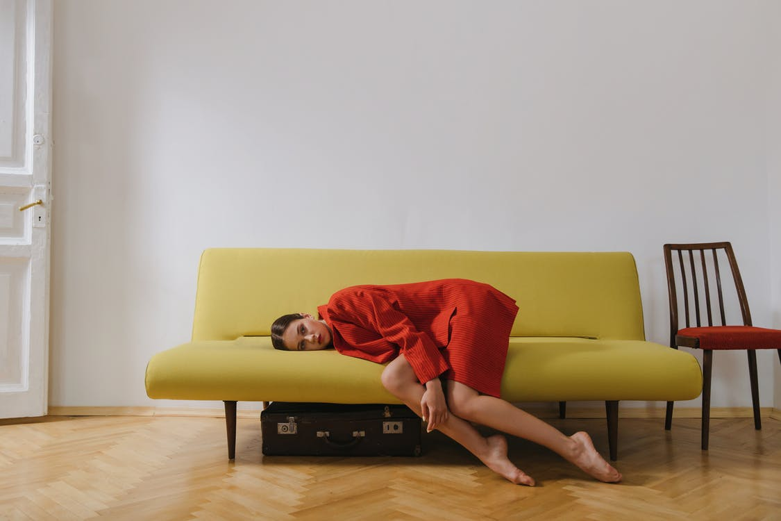 Woman in Red Dress Lying on Yellow Couch