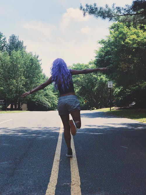 Woman in Blue Long Sleeve Shirt and Black Denim Shorts Standing on Gray Asphalt Road during