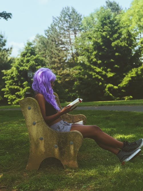 Purple Haired Woman in Brown Dress Sitting on Brown Wooden Bench