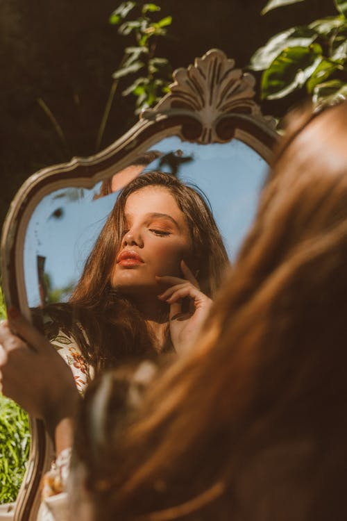 Woman reflecting in mirror in nature