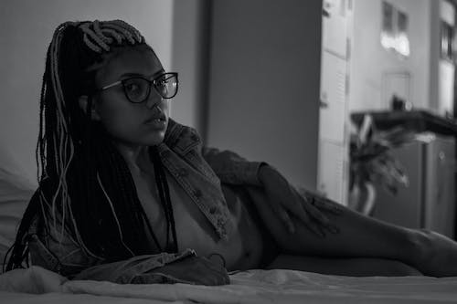 Black and white of alluring young ethnic lady with long braids in eyeglasses and denim jacket on naked body lying on comfortable bed at home