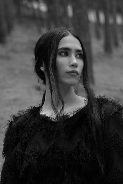 Black and white attractive calm female with long dark hair wearing fluffy sweater standing in woods and looking away