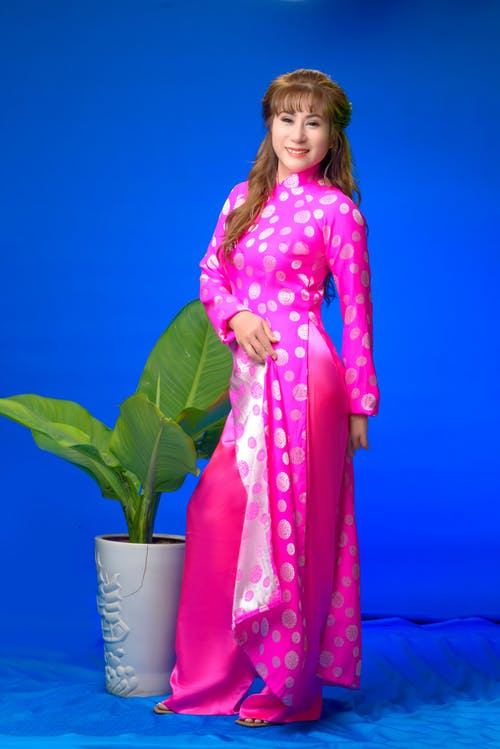 Woman in Pink and White Polka Dot Robe Holding Green Plant