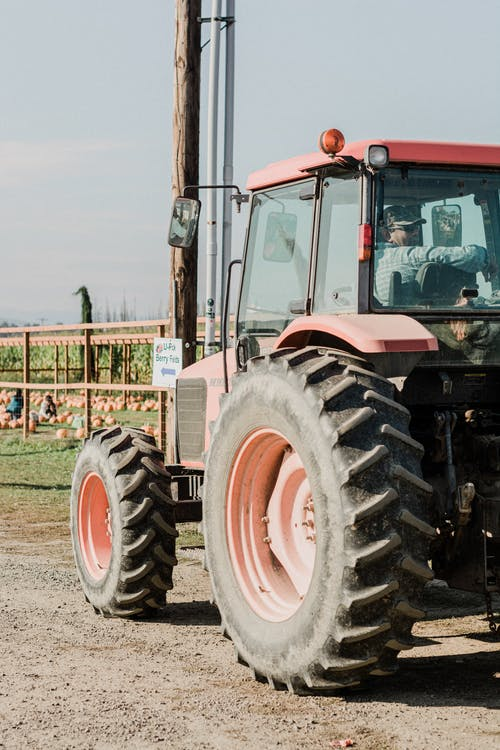 Orange and Black Tractor on Green Grass Field