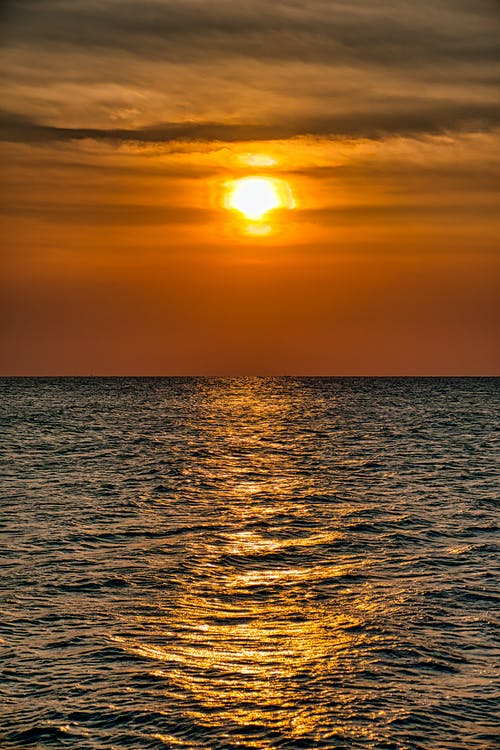 Picturesque view of rippled ocean with horizon under colorful cloudy sky with shiny sunlight in evening