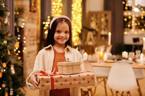 Shallow Focus of a Girl Smiling While Holding Her Christmas Presents