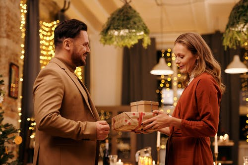 Woman Giving Christmas Presents to Her Husband