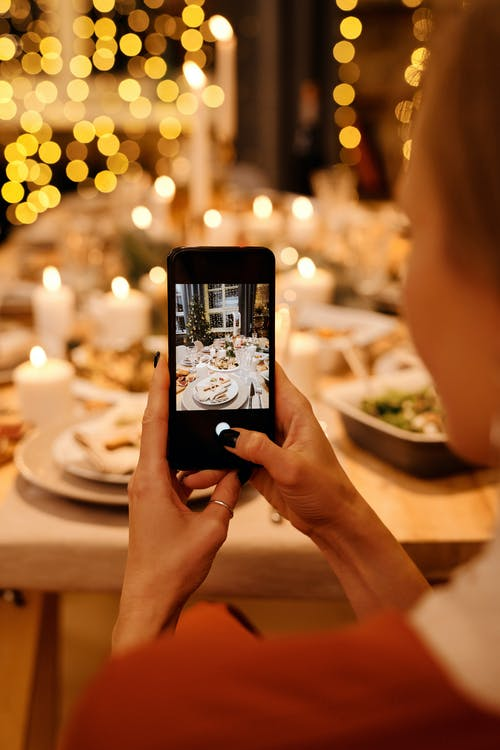Woman Taking Photo of Food on Table