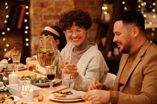 Woman in Gray Sweater Sitting Beside Man in Brown Blazer