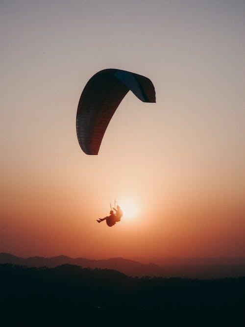 Paraglider flying in sunset sky