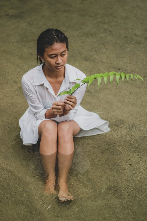 From above full body barefoot attractive Asian female wearing wet white dress holding verdant fern stem and looking away in pleasant thoughts while resting on sandy river shore