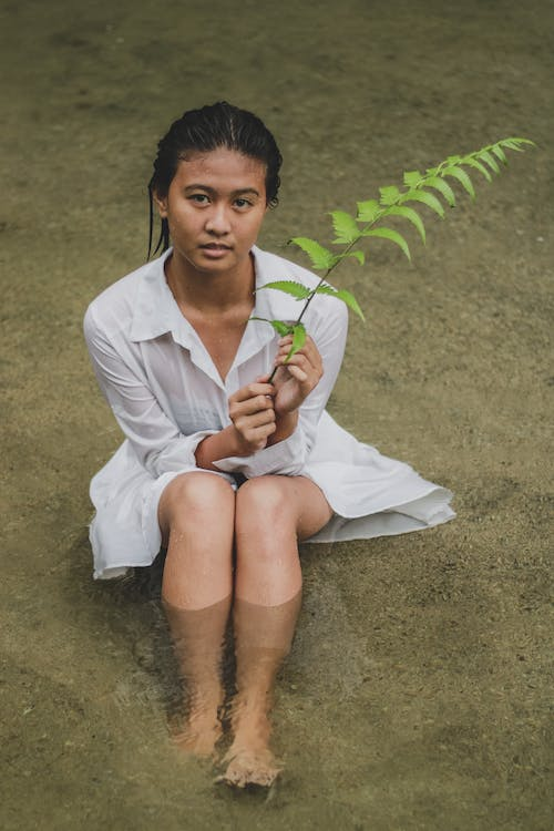 Young Asian woman with fern branch sitting in shallow water