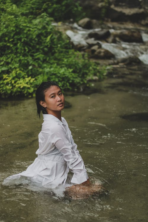 Serene Asian woman sitting in tranquil river